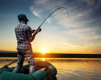 Fisherman. Mature man fishing from the boat on the pond at sunset Royalty Free Stock Image