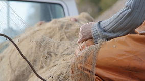 A fisherman mending his fishing net Stock Images