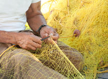 Fisherman Mending His Fishing Net in Greece. A fisherman mending his yellow fishing net on his boat in a Greek island royalty free stock images