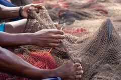 Fisherman mending nets. Burgundy, black, white, gray. Fisherman mending nets. Fishing nets. Floats on the fishing net royalty free stock photo