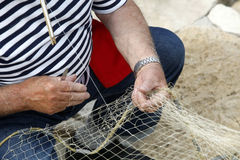 Fisherman Mending Nets. An old fisherman sits, mending his fishing net Royalty Free Stock Photo