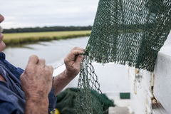 Fisherman mending nets. Weathered hands of fisherman mending net on a fishing boat Stock Photography