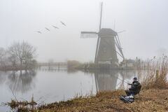 Fisherman at the misty and calm windmill sunrise