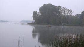 Fisherman in misty early morning on lake at country region. 4K. Lonely fisherman in misty early morning on lake at country region. 4K UHD video clip stock footage