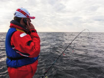 Fisherman with mobile phone stock images