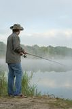 Fisherman on a morning foggy lake Stock Photos