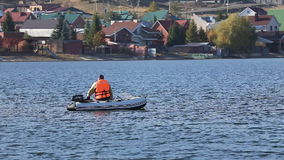 A fisherman in a motor boat fishing stock footage