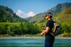 Fisherman on the mountain river at the nice summer day. Trout fly fishing in the mountain river with mountains in background royalty free stock photo