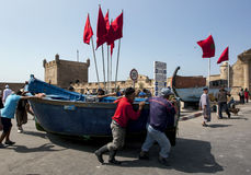 Fisherman move a boat in the port of Essaouira in Morocco. Stock Images