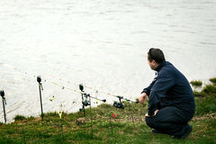 Fisherman near his rods waiting to catch Royalty Free Stock Photos
