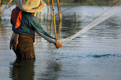 Fisherman with net. Fisherman fishing with large net in lake stock images