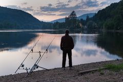 Fishing adventures, carp fishing at sunset. Fisherman next to the fishing equipment observes the sunset on the shore of a lake. View from behind and copy space royalty free stock photos