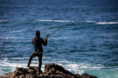 Fisherman on Northern California Coast. A fisherman casts off the scenic and rugged coastline of northern California Stock Image