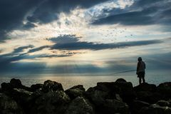 The silhouette of a fisherman, fishing off the ocean shore at sunrise. a beautiful sky full of clouds and rays of the sun stock photos
