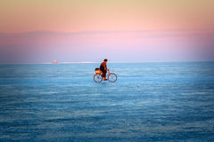 Fisherman on old bike goes to sea through dangerous ice with a crack Royalty Free Stock Photo