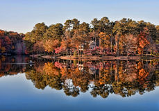Fisherman On Calm Lake By Home In Autumn Stock Images