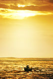 Fisherman paddle boat in sunset Stock Photography