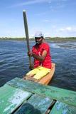 A fisherman paddles across Pottuvil Lagoon in Sri Lanka. Stock Photography