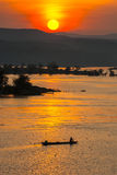 Fisherman paddling rowboat to fishing with sunset, Silhouette Stock Photos