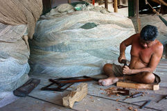 Fisherman pare wood at fishing net shop. CA MAU, VIET NAM- JUNE 29 royalty free stock photos