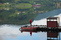 Fisherman on a pier on a fjord Royalty Free Stock Images