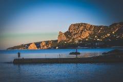 Fisherman on pier near mountain-cat morning Royalty Free Stock Photo