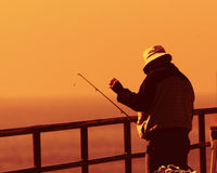 Fisherman on pier at sunset Royalty Free Stock Images
