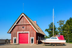 Fisherman (piscatorial) house with a sailing boat aside Royalty Free Stock Photo