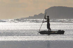Fisherman Poling at Sunrise Stock Image