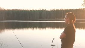 Fisherman on the pond. A young guy with dreads in glasses in a t-shirt fishing fish rod. Fisherman on the pond. A young guy with dreads in glasses in a t-shirt stock video
