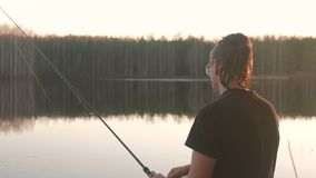 Fisherman on the pond. Young guy with dreads in glasses in a t-shirt fishing fish with rod. Fisherman on the pond. Young guy with dreads in glasses in a t-shirt stock video
