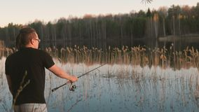 Fisherman on the pond. Young guy with dreads in glasses in a t-shirt fishing fish with rod. Fisherman on the pond. Young guy with dreads in glasses in a t-shirt stock footage
