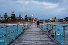 A fisherman on the Port Noarlunga Jetty looking back towards the. Shore at Port Noarlunga South Australia stock photography