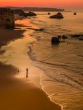 Fisherman. Portuguese fisherman fishing at sunrise from the seashore. Coast Algarve.Portugal Stock Photos
