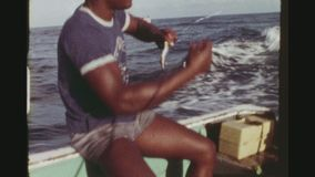 Fisherman Prepairing Bate. REPUBLIC OF TRINIDAD, TOBAGO, APRIL 1976. Two Shot Sequence Of A Native Fisherman Hooking Sardines As Bate In A Small Boat And POV Of stock video