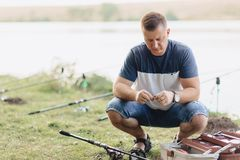 Fisherman prepares snap for catching carp at lake in summer stock photos