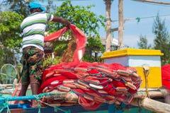 Fisherman preparing fishing net on a boat Stock Image