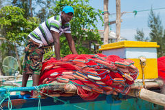 Fisherman preparing fishing net on a boat Stock Photo