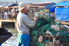 A fisherman is preparing his fishing net for a new working day at a local seaport Stock Photography