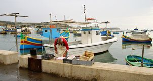 Fisherman preparing a sea cat. MARSAXLOKK VILLAGE, ISLAND OF MALTA - NOVEMBER 2, 2014. Rainy day in Marsaxlokk, ancient fishing village at the Mediterranean Sea Stock Photo