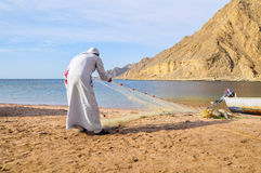 The fisherman pulling the net. The fisherman is pulling a fishing net from the sea Stock Images