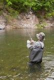 Fisherman pulls caught salmon Royalty Free Stock Photo