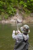 Fisherman pulls caught salmon Stock Image