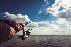 Closeup of a boys hand holding a fishing rod and reel. The fisherman pulls the fish out of the water on the lake. Closeup of a boys hand holding a fishing rod Royalty Free Stock Photography