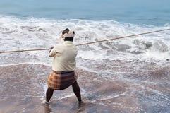 Fisherman pulls fishing net on Samudra beach in Kovalam stock photography
