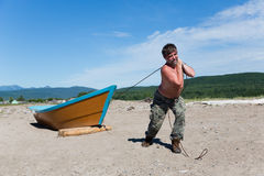 Fisherman pulls a heavy wooden boat Royalty Free Stock Photos
