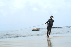 Fisherman pulls his fishing boat royalty free stock photography