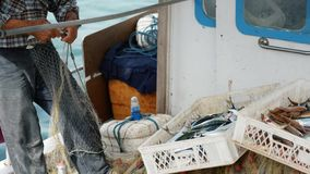 A fisherman pulls out a fish catch from fishing nets and throw into basket. Elderly sailor in the port of Bodrum, Turkey stock video footage