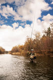 Fisherman pulls trout on the river Stock Photos