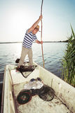Fisherman pushing boat from the river bank Royalty Free Stock Images
